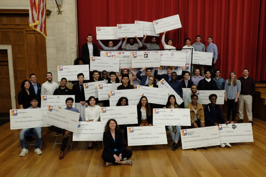 31 high school students pose with their mentors and giant scholarship checks